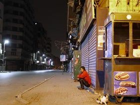 A man sits on the side of a deserted street in Cairo during a night-time curfew, on March 25, 2020.