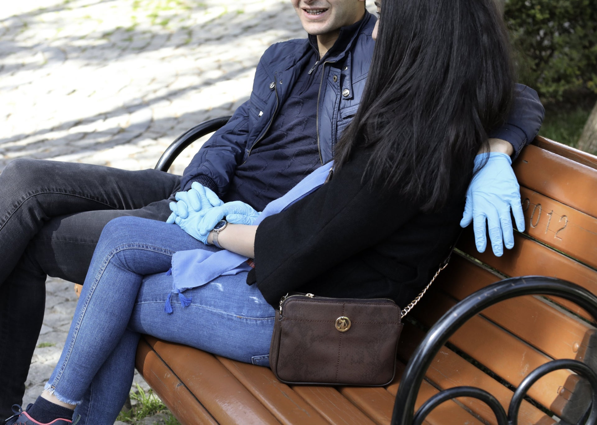 A couple wear protective gloves as they sit together in a public garden amid the coronavirus outbreak, in Ankara, Turkey.
