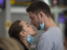 A couple kiss at the Barcelona airport, Spain, last week. The coronavirus epidemic differs from the sort of national stress that's caused by war.