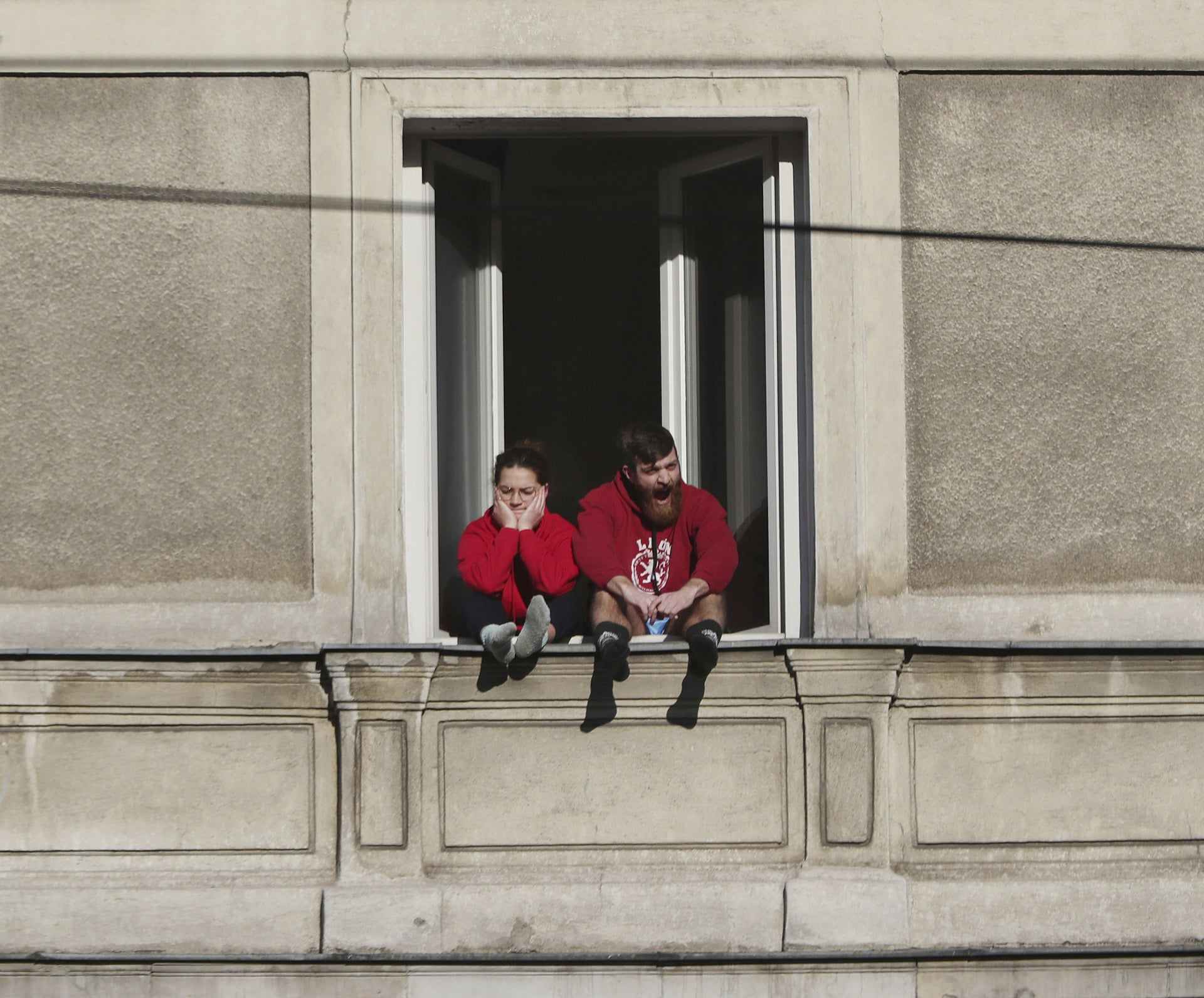 A couple bored with the government-required national isolation at home due to the spreading coronavirus, sits in window in downtown Warsaw, Poland.