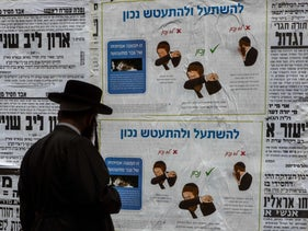 An ultra-Orthodox man in the Jerusalem neighborhood of Mea She'arim reading a coronavirus poster informing people how best to cough or sneeze, March 27, 2020.