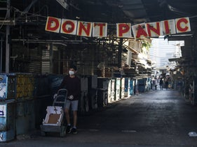 "A sign reads ""Don't panic"" above the Carmel Market shops closed during Israel's coronavirus lockdown in Tel Aviv, March 25, 2020."