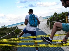 Joggers trespass at the Miami Beach in Miami, closed to prevent the spread of coronavirus. March 19, 2020