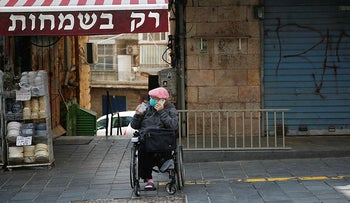 A woman sits in a mostly closed market in Jerusalem, March 22, 2020.