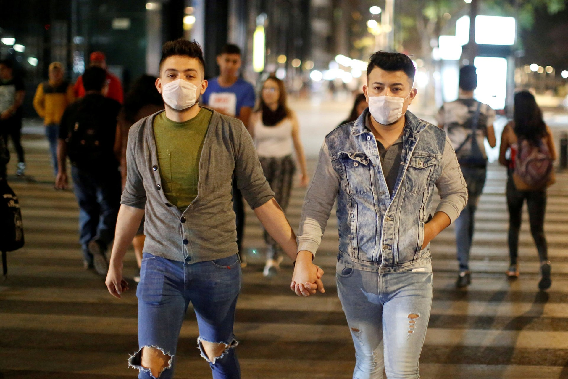 A couple hold hands as the coronavirus disease outbreak continues in downtown of Mexico City, Mexico.