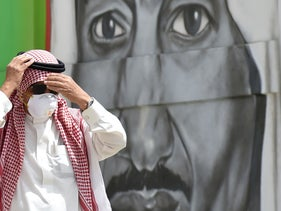A pedestrian wearing a protective mask as a coronavirus precaution walks past a mural depicting King Salman. Riyadh, Saudi Arabia, March 15, 2020