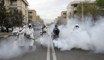 Firefighters disinfect the streets in Tehran, March 18, 2020