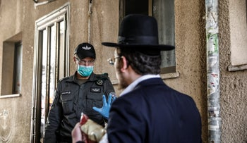 An ultra-Orthodox man is stopped by police in the Tel Aviv suburb of Bnei Brak, March 30, 2020.