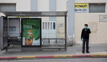 A man waits at a bus stop in Tel Aviv, March 30, 2020