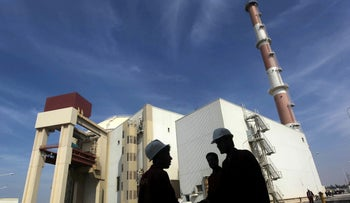 Iranian workers stand in front of the Bushehr nuclear power plant, about 1,200 km (746 miles) south of Tehran, Iran, October 26, 2010.