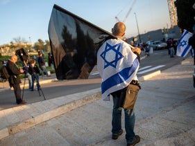 A protester wrapped in an Israeli flag holds a black flag during a demonstration against then Knesset Speaker Yuli Edelstein, Jerusalem, March 25, 2020.