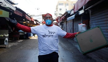 A market seller reacts during an Israel police operation to close the Carmel Market, in central Tel Aviv, Israel, March 22, 2020.
