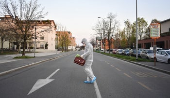 A medical staffer wearing protective gear, part of a special unit performing house calls in Bergamo, northern Italy, one of the areas worse-affected by coronavirus, March 25, 2020.