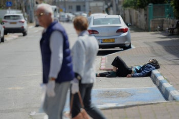 A couple wearing disposable gloves pass by a homeless man in the city of Acre, northern Israel.