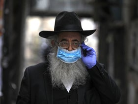 An Ultra-Orthodox Jew wearing a protective mask walks on an empty street in one of the ultra-Orthodox Jewish neighborhoods in Jerusalem.  March 31, 2020