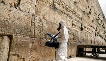 A laborer sanitizes the stones of the Western Wall as part of measures to prevent the spread of the coronavirus diseases, in Jerusalem's Old City, March 31, 2020.