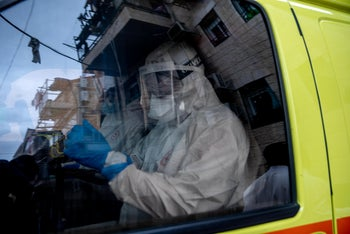 A paramedic in full protective gear inside an ambulance, Meah Shearim, Jerusalem, March 31, 2020.