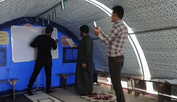 Ahmed Hadaja, a 21-year-old medic and volunteer Arabic teacher, records with other teachers a video lesson to be sent for student in Atmeh camp, near the Turkish border, Syria, March 30, 2020.