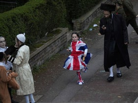 A Jewish girl in a Union Flag dress running down the street during the annual Purim holiday in Stamford Hill, London, March 10, 2020.