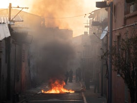 A plastic barrier burns in the middle of a street in Jaffa after clashes between police officers and local residents, April 1, 2020