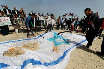 Palestinians in Gaza burn an Israeli flag during an event marking Land Day near the Israel-Gaza border. Mass rallies were cancelled. March 30, 2020