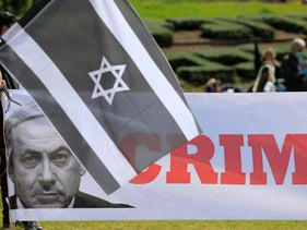 Anti-government protester waves an Israeli flag painted black at a demonstration in front of the Knesset. March 25, 2020