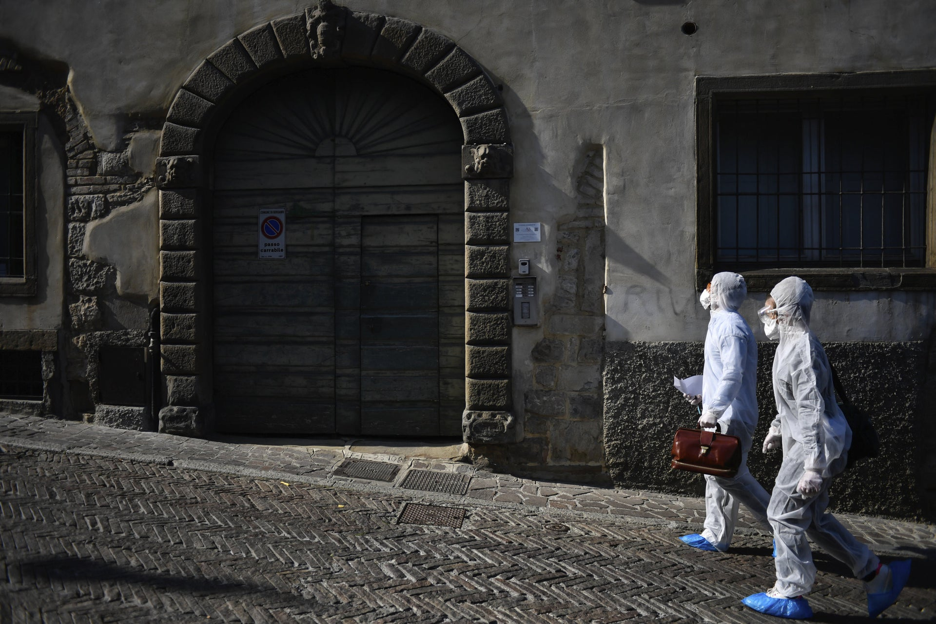 Medical staffers wearing protective gear, part of a special unit performing house calls, walk in Bergamo, northern Italy, one of the areas worse-affected by coronavirus, March 25, 2020.