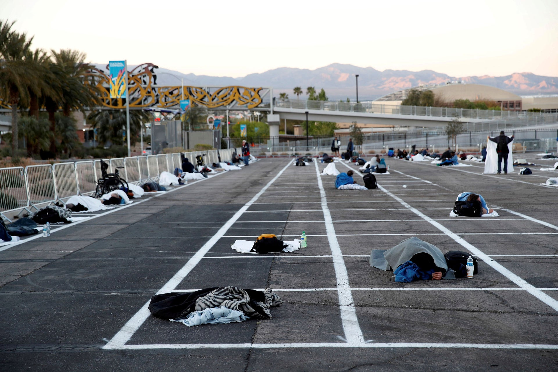 Homeless people sleep in a temporary parking lot shelter at Cashman Center, with spaces marked for social distancing to help slow the spread of the coronavirus in Las Vegas, Nevada, March 30, 2020.
