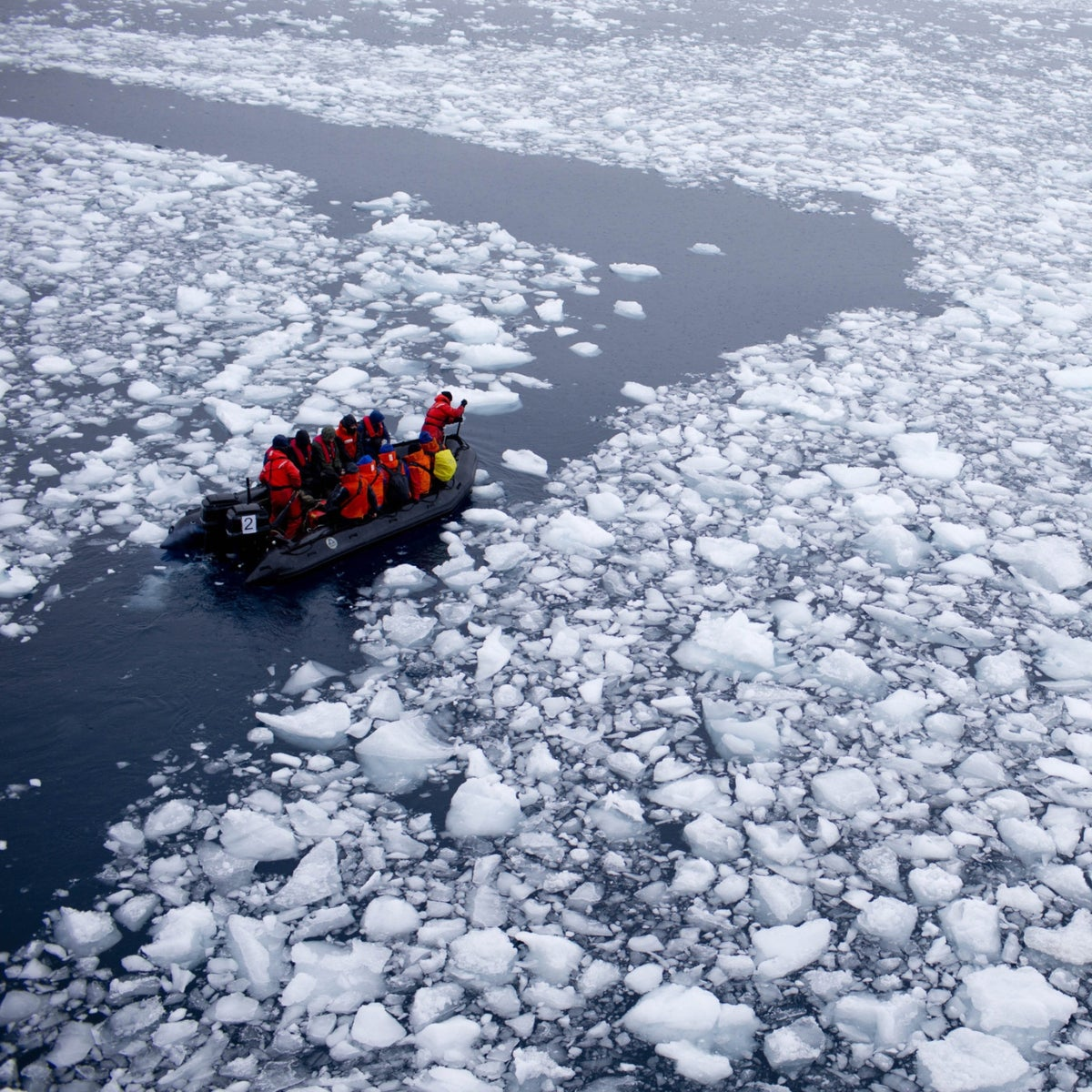 A team of scientists heads through the melting ice of Antartica as it approaches a Chilean station there, in 2015.
