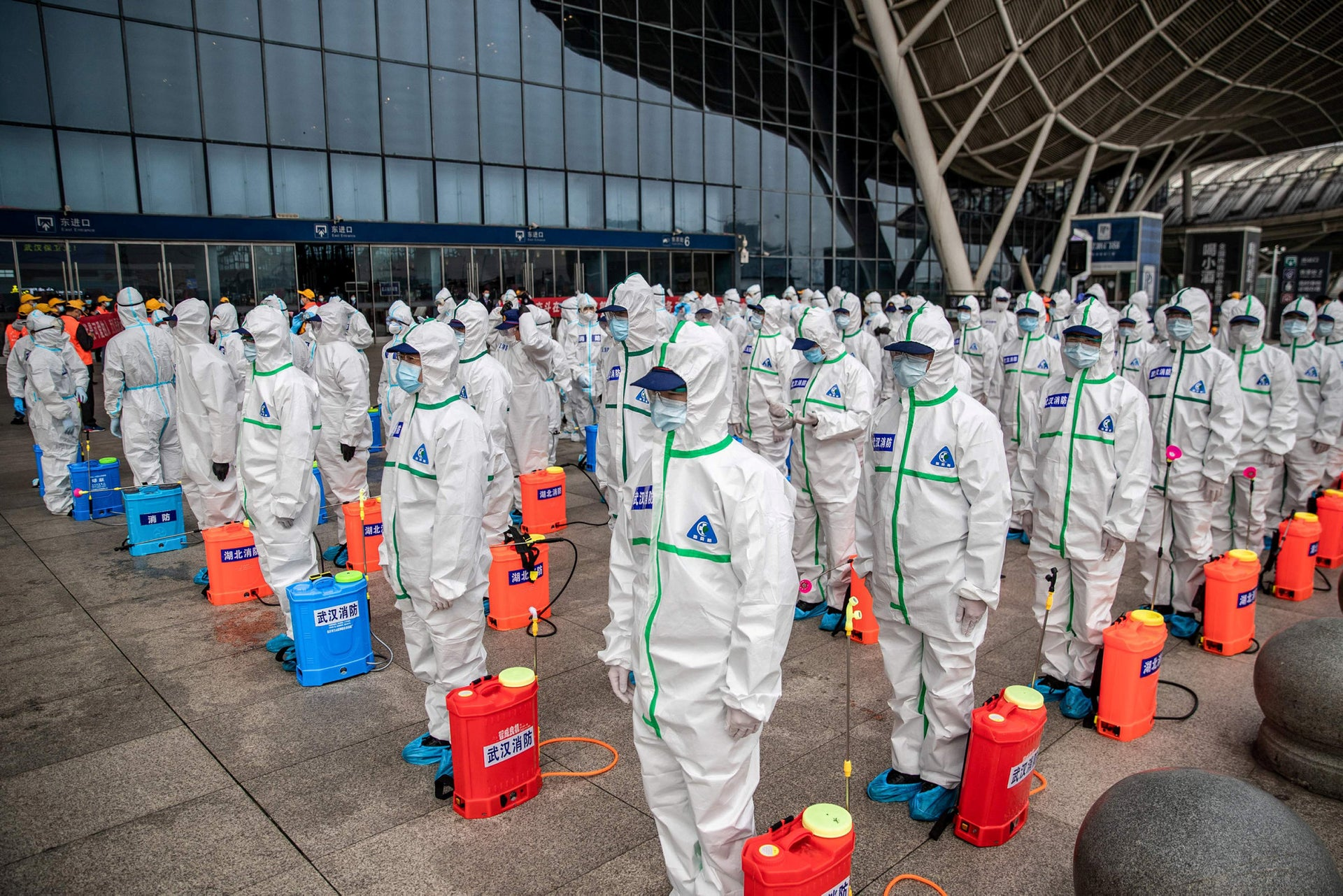 In this file photo staff members line up at attention as they prepare to spray disinfectant at Wuhan Railway Station in Wuhan in China's central Hubei province on March 24, 2020.