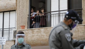Children look on from a balcony as Israeli police officers enforce movement restrictions during the coronavirus outbreak, Bnei Brak, Israel, April 1, 2020.