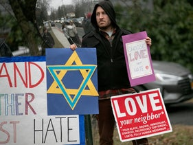 A man holds a sign outside the home of Rabbi Chaim Rottenberg in the Rockland County community of Monsey, N.Y.following a stabbing attack there.