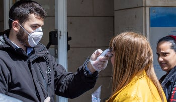 A woman gets her temperature tested at the entrance to the National Insurance building in Jerusalem, March 2020.