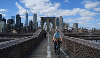 A masked cyclist rides on Brooklyn Bridge as the coronavirus outbreak continues, New York, April 1, 2020.