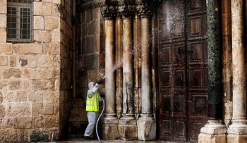A worker disinfects the doors of the closed Church of the Holy Sepulchre in Jerusalem's Old City, March 30, 2020.
