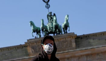 A man wears a face mask during a protest demanding to take refugees from camps affected by the coronavirus outbreak, in front of Brandenburg Gate in Berlin, Germany.