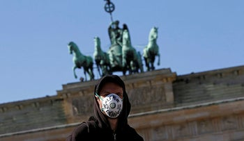 A man wears a face mask during a protest demanding to take refugees from camps affected by the coronavirus in Berlin, Germany April 5, 2020.
