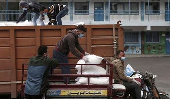 Palestinian workers at the United Nations Relief and Works Agency for Palestinian Refugees (UNRWA) wearing protective masks and gloves, transport food aid rations to be henceforth delivered to refugee family homes rather than distributed at a UN a center, in Gaza City, on March 31, 2020, due to the COVID-19 pandemic.