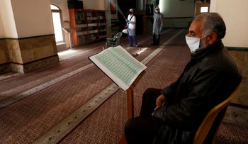 A Palestinian reads Koran as a worker disinfects a mosque as a preventive measure against the coronavirus, in Ramallah in the West Bank, March 7, 2020.