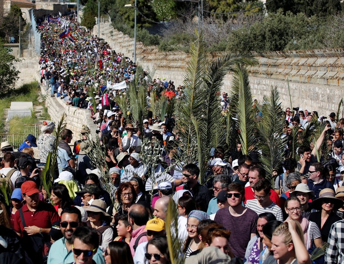 Catholic faithful hold palm fronds during a Palm Sunday procession on the Mount of Olives in Jerusalem, March 25, 2018.