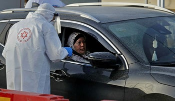 A paramedic of Israel's Magen David Adom handles a swab to test for coronavirus at a drive-thru testing site in Tamra, March 31, 2020.