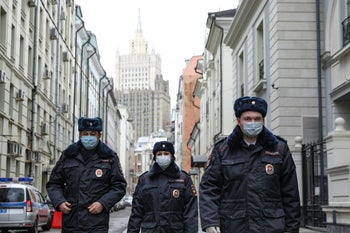 Russian police officers wearing face masks to protect against coronavirus, patrol an almost empty Arbat street in Moscow, Russia. April 2, 2020