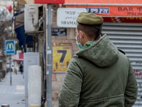 A soldier stands in Bnei Brak after a closure was imposed on the city, April 1, 2020.