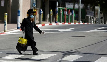 An ultra-Orthodox Jewish man wears a face mask while crossing a street in Bnei Brak, Israel April 3, 2020.