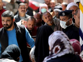 A policeman wearing a mask stands guard as Palestinians wait outside a bank to withdraw cash in Gaza City, March 29, 2020.