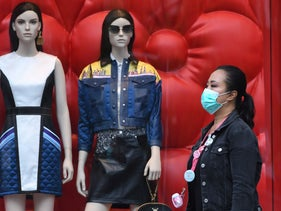 A woman wearing a face mask as she walks next to a store in a shopping district on Orchard Road, Singapore, April 5, 2020.