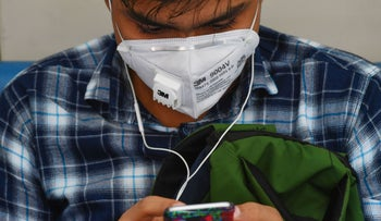 A man wearing a protective face mask amid the coronavirus pandemic while looking in his phone, March 2020.