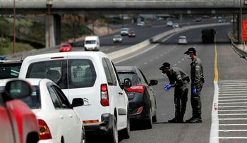 Border policemen chat to a driver at a roadblock set-up by police as they begin to enforce a national lockdown to fight the spread of the coronavirus April 7, 2020.