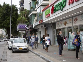 Shopper line up, keeping their distance, outside a supermarket in Tel Aviv on Monday.