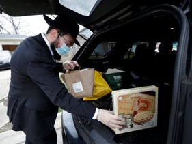 Rabbi Yaakov Kotlarsky places Passover Seder to go packages into his car at Chabad Jewish Center in Arlington Heights, Illinois, April 7, 2020.